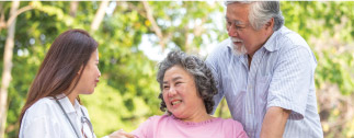 Patient and spouse outdoors with caregiver